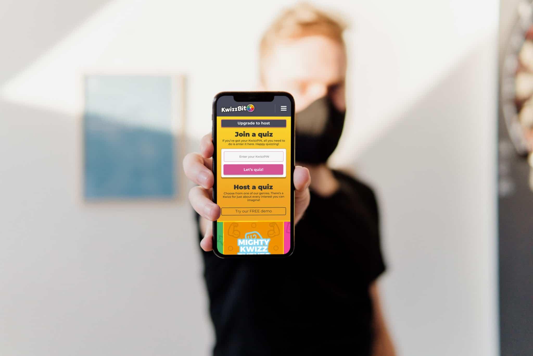 man wearing mask mobile phone displaying KwizzBit website