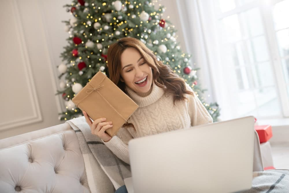 Happy woman opening a Christmas present on a video call
