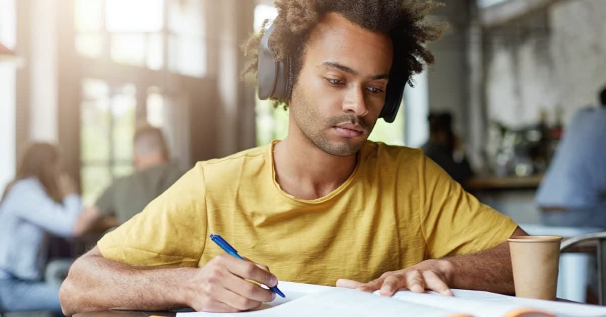 person of colour in yellow t-shirt listening to general knowledge podcasts