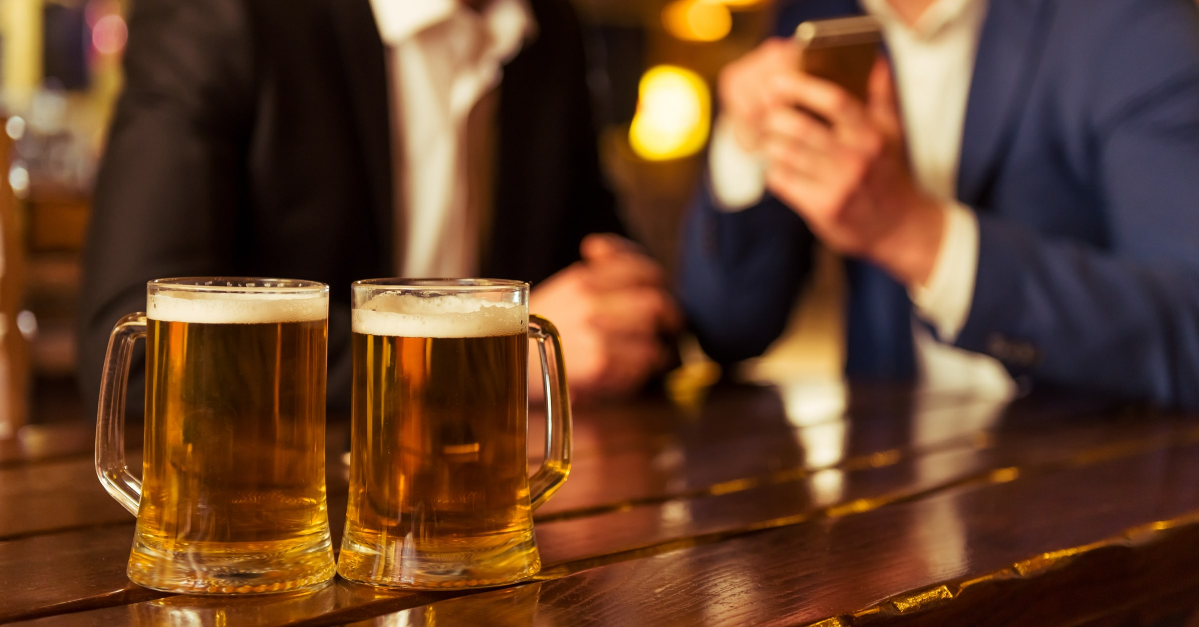 two beers on table and business men using digital pub technology