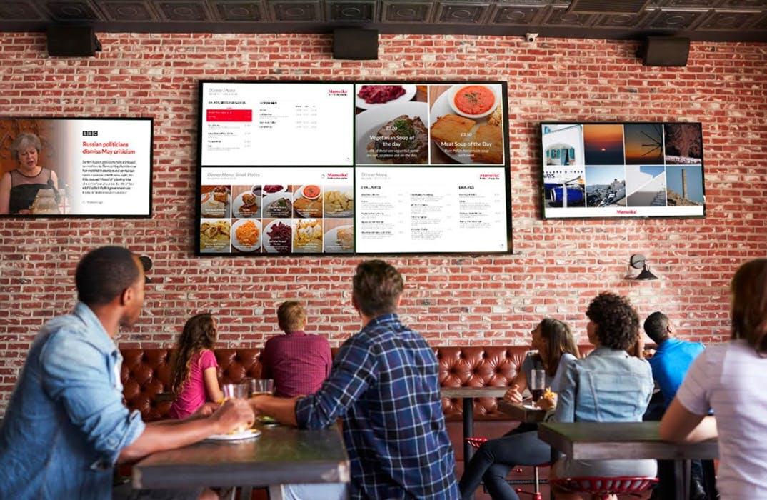 Digital signage screens attached to wall in digital pub