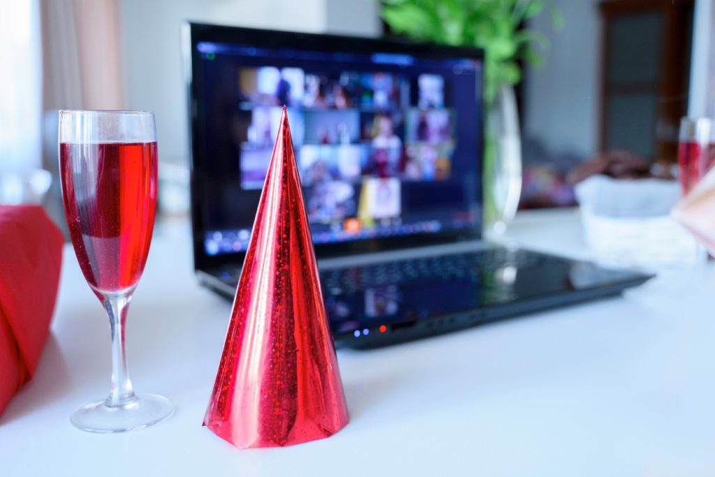 red wine, party hat and a virtual event on a laptop